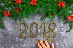 Κλάδοι του FIR με τους κώνους και κόκκινα τόξα πάνω από ένα γκρίζο συγκεκριμένο υπόβαθρο Νέα Χριστούγεννα έτους Κείμενο 2018 χρυσ Στοκ φωτογραφίες με δικαίωμα ελεύθερης χρήσης