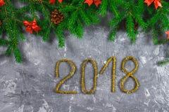 Κλάδοι του FIR με τους κώνους και κόκκινα τόξα πάνω από ένα γκρίζο συγκεκριμένο υπόβαθρο Νέα Χριστούγεννα έτους Κείμενο 2018 χρυσ Στοκ Εικόνα