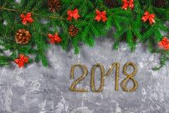 Κλάδοι του FIR με τους κώνους και κόκκινα τόξα πάνω από ένα γκρίζο συγκεκριμένο υπόβαθρο Νέα Χριστούγεννα έτους Κείμενο 2018 χρυσ Στοκ Εικόνες