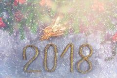 Κλάδοι του FIR με τους κώνους και κόκκινα τόξα πάνω από ένα γκρίζο συγκεκριμένο υπόβαθρο Νέα Χριστούγεννα έτους Κείμενο 2018 χρυσ Στοκ εικόνες με δικαίωμα ελεύθερης χρήσης
