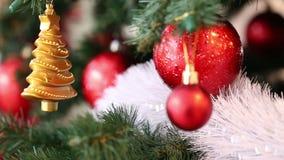 Κλάδοι του FIR που διακοσμούνται με τα κόκκινα και χρυσά παιχνίδια Χριστουγέννων, άσπρη λάμποντας γιρλάντα φιλμ μικρού μήκους