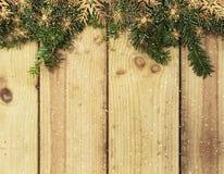 Κλάδοι χριστουγεννιάτικων δέντρων στο ξύλινο υπόβαθρο με την επικάλυψη χιονιού Στοκ Εικόνες
