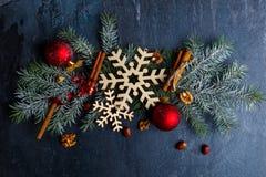 Κλάδος δέντρων με snowflakes, τα παιχνίδια, τα ραβδιά κανέλας και τα ξύλα καρυδιάς Σε μια σκοτεινή ανασκόπηση Στοκ φωτογραφία με δικαίωμα ελεύθερης χρήσης
