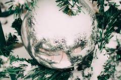 κλάδος με το χιόνι του χριστουγεννιάτικου δέντρου με την ασημένια σφαίρα Χριστουγέννων υπαίθρια στοκ εικόνα με δικαίωμα ελεύθερης χρήσης