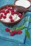 Κλάδος σμέουρων με την ξινή κρέμα στάρπης μούρων στο πήλινο είδος στο μπλε υπόβαθρο υφασμάτων Στοκ φωτογραφία με δικαίωμα ελεύθερης χρήσης