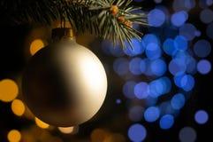 Κλάδος χριστουγεννιάτικων δέντρων με τη σφαίρα μαργαριταριών στο θολωμένο ανοικτό μπλε και χρυσό υπόβαθρο σημείων στοκ εικόνα