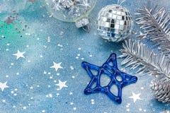 Κλάδος χριστουγεννιάτικων δέντρων με τις διακοσμήσεις στο μπλε υπόβαθρο Στοκ Φωτογραφία