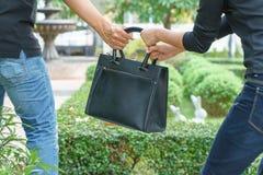Κλέβοντας και τραντάζοντας τσάντα κλεφτών από τη γυναίκα στο δημόσιο πάρκο Στοκ φωτογραφία με δικαίωμα ελεύθερης χρήσης