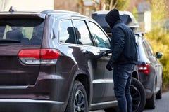 Κλέφτης αυτοκινήτων στο αυτοκίνητο στην κλοπή αυτοκινήτων στοκ φωτογραφίες