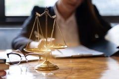 Κλίμακες της δικαιοσύνης στο ξύλινο επιτραπέζιο υπόβαθρο με τους επαγγελματικούς θηλυκούς δικηγόρους που εργάζονται στις εταιρίες στοκ εικόνα