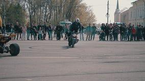 Κλίσεις μοτοσυκλετιστών σε μια μοτοσικλέτα σε έναν κύκλο με μια πλάτη ποδιών Δροσίστε τις ακροβατικές επιδείξεις σε μια μοτοσικλέ απόθεμα βίντεο