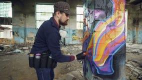 Κλίση-επάνω στον πυροβολισμό των δημιουργικών γενειοφόρων γκράφιτι ζωγραφικής τύπων στη χαλασμένη στήλη μέσα στο παλαιό κτήριο με απόθεμα βίντεο