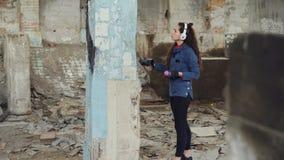 Κλίση-επάνω στον πυροβολισμό των λεπτών γκράφιτι σχεδίων ζωγράφων κοριτσιών σύγχρονων στην υψηλή στήλη στην αποθήκη εμπορευμάτων  φιλμ μικρού μήκους