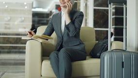 Κλίση επάνω της ξανθής εύθυμης συνεδρίασης επιχειρηματιών στην πολυθρόνα στο λόμπι ξενοδοχείων που μιλά το κινητό τηλέφωνο και πο απόθεμα βίντεο