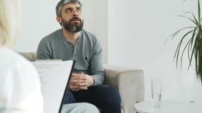 Κλίση επάνω του υ ατόμου που μιλά για τα οικογενειακά προβλήματά του με το θηλυκό ψυχολόγο στο γραφείο της στο εσωτερικό απόθεμα βίντεο