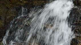 Κλίση κάτω του καταρράκτη που πέφτει και χτυπημένου που καταβρέχει βράχου στον ποταμό φιλμ μικρού μήκους