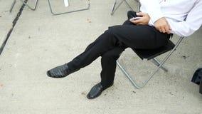 Κλασικά μαύρα παπούτσια ατόμων ` s το άτομο κάθεται με το τηλέφωνο στην καρέκλα 4K απόθεμα βίντεο