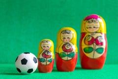 Κλασική γραπτή σφαίρα ποδοσφαίρου ποδοσφαίρου και τρεις κόκκινες κίτρινες ρωσικές να τοποθετηθεί κούκλες στοκ εικόνα με δικαίωμα ελεύθερης χρήσης