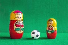 Κλασική γραπτή σφαίρα ποδοσφαίρου ποδοσφαίρου και τρεις κόκκινες κίτρινες ρωσικές να τοποθετηθεί κούκλες στοκ εικόνα