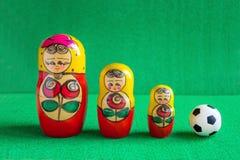 Κλασική γραπτή σφαίρα ποδοσφαίρου ποδοσφαίρου και τρεις κόκκινες κίτρινες ρωσικές να τοποθετηθεί κούκλες στοκ φωτογραφίες