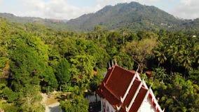 Κλασικός βουδιστικός ναός μεταξύ του δασικού άνωθεν κλασικού βουδιστικού μοναστηριού άποψης κηφήνων μεταξύ των πράσινων δέντρων κ απόθεμα βίντεο