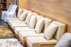 Κλασικός κρεμώδης και ξύλινος καναπές στο σαλόνι τουριστών της Μπανγκόκ για το wel στοκ φωτογραφίες