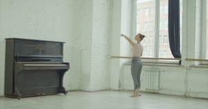 Κλασικός χορευτής μπαλέτου που ασκεί το demi plie στην μπάρα απόθεμα βίντεο