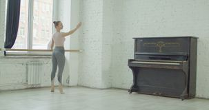 Κλασικός χορευτής μπαλέτου που ασκεί releve στην μπάρα απόθεμα βίντεο