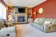 Κλασικό άνετο εσωτερικό καθιστικών με την εστία και τον κόκκινο τοίχο. Στοκ Φωτογραφίες