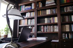 Κλασικό γραφείο ύφους με τη μεγάλη βιβλιοθήκη στοκ εικόνα