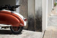 Κλασικό ιταλικό μηχανικό δίκυκλο από ένας χτυπημένος τοίχος που σταθμεύει στοκ φωτογραφία με δικαίωμα ελεύθερης χρήσης