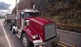 Κλασικό κόκκινο μεγάλο ημι φορτηγό εγκαταστάσεων γεώτρησης με το βήμα - κάτω από το ημι ρυμουλκό δια στοκ φωτογραφίες με δικαίωμα ελεύθερης χρήσης