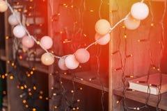 Κλασσικό ξύλινο ράφι με το εκλεκτής ποιότητας βιβλίο και κενό πλαίσιο με τα πορτοκαλιά φω'τα γιρλαντών σφαιρών Στοκ Φωτογραφία