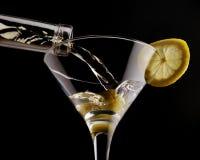 Κλασσικό martini στο κατεψυγμένο γυαλί πέρα από το μαύρο υπόβαθρο, που διακοσμείται με την ελιά και το λεμόνι Στοκ φωτογραφία με δικαίωμα ελεύθερης χρήσης