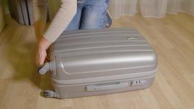 Κλείνοντας σύνδεσμος φερμουάρ κοριτσιών στη βαλίτσα ταξιδιού Γυναίκα που τραβά τη βαλίτσα φερμουάρ απόθεμα βίντεο