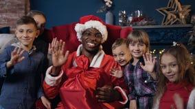 Κλείστε αυξημένος Άγιου Βασίλη και των χαριτωμένων παιδιών που κυματίζουν στη κάμερα φιλμ μικρού μήκους