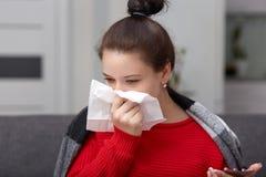 Κλείστε αυξημένος ανεπαρκή sneezes γυναικών και τυλίγει την τρέχοντας μύτη, στο coverlet, κρατά το κινητό τηλέφωνο και ο ιστός, έ στοκ φωτογραφία