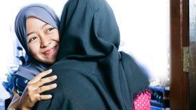 Κλείστε αυξημένος δύο Hijab της γυναίκας αγκαλιάζοντας έναν μουσουλμανικό φίλο στοκ φωτογραφίες