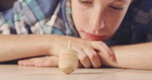 Κλείστε αυξημένος ενός αγοριού που περιστρέφει ένα Hanukka dreidel στο πάτωμα φιλμ μικρού μήκους