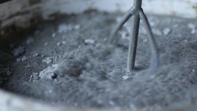 Κλείστε αυξημένος ενός κάδου του τσιμέντου, των εργαζομένων υλικών και του νερού μιγμάτων χαλαρών για να παραγάγει το τσιμέντο απόθεμα βίντεο