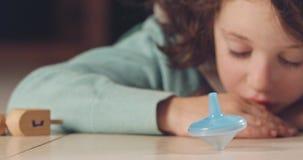 Κλείστε αυξημένος ενός κοριτσιού που περιστρέφει ένα Hanukka dreidel στο πάτωμα απόθεμα βίντεο