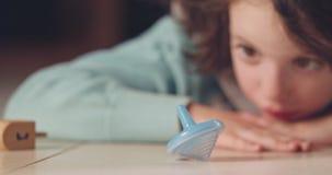 Κλείστε αυξημένος ενός κοριτσιού που περιστρέφει ένα Hanukka dreidel στο πάτωμα φιλμ μικρού μήκους