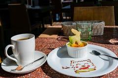Κλείστε αυξημένος ενός πιάτου του creme brulle και ενός φλιτζανιού του καφέ στοκ φωτογραφία με δικαίωμα ελεύθερης χρήσης