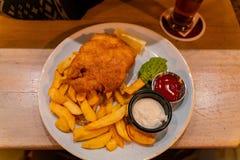 Κλείστε αυξημένος ενός πιάτου των ψαριών και των τσιπ στοκ φωτογραφίες