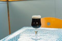 Κλείστε αυξημένος ενός ποτηριού της σκοτεινής μπύρας στοκ φωτογραφία