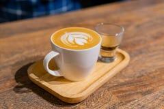 Κλείστε αυξημένος ενός φλυτζανιού του καφέ Latte στοκ εικόνα