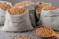 Κλείστε αυξημένος λίγου σάκου φιαγμένου από ύφασμα λινού που γεμίζουν με το ξηρό καφετί φαγόπυρο, ξύλινο κουτάλι με τα ακατέργαστ στοκ εικόνες