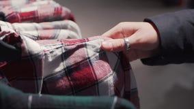 Κλείστε αυξημένος μιας γυναίκας επιλέγει το πουκάμισο καρό σε μια μπουτίκ μόδας απόθεμα βίντεο