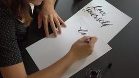 Κλείστε αυξημένος μιας νέας καλλιγραφίας γυναικών γράφοντας σε χαρτί χρησιμοποιώντας την τεχνική εγγραφής Γράφει την αγάπη οι ίδι απόθεμα βίντεο