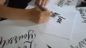 Κλείστε αυξημένος μιας νέας καλλιγραφίας γυναικών γράφοντας σε χαρτί χρησιμοποιώντας την τεχνική εγγραφής Γράφει την αγάπη οι ίδι φιλμ μικρού μήκους